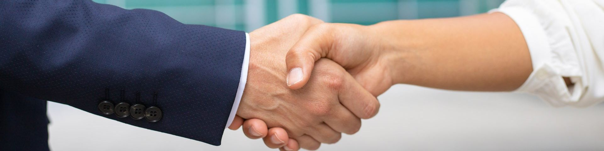 A close up of a handshake between someone wearing a blue suit and a white shirt.